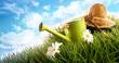 Gießkanne und Strohut liegen im Gras
